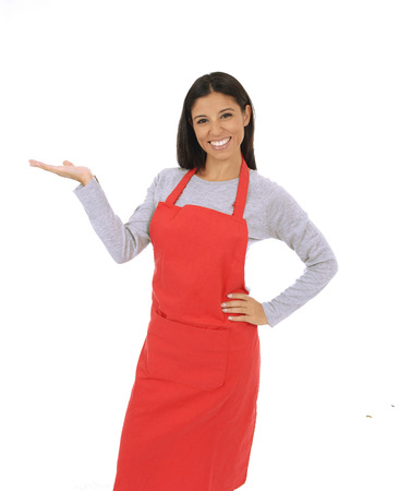 corporate portrait of young attractive hispanic home cook woman in red apron and hat posing happy and smiling presenting menu isolated on white background in chef and successful cooking