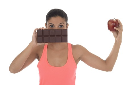 young attractive hispanic woman in fitness top holding apple fruit and chocolate bar in her hands in diet dilemma sweet tasty unhealthy food against healthy nutrition choice
