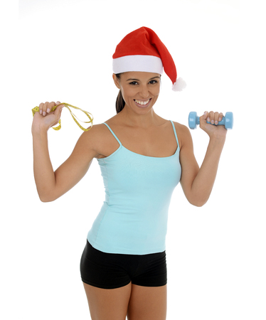 young beautiful and exotic hispanic woman in Christmas Santa hat holding weight and measure tape isolated on white background in healthy fitness and diet New Year resolution concept Stock Photo
