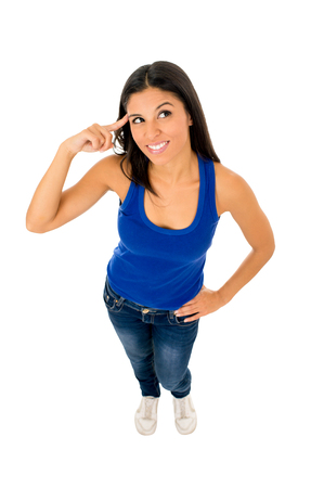 indecisive: young attractive hispanic woman smiling happy in casual top and jeans pointing her head thinking and wondering confused in doubt isolated on white background