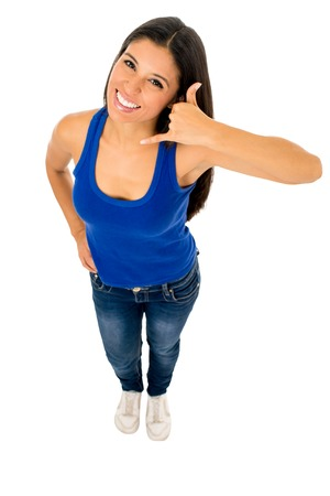 young beautiful and exotic hispanic woman in tank top and jeans doing call me telephone sign with her hand smiling happy isolated on white background Stock Photo