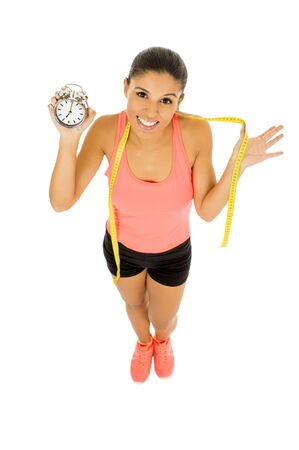 young beautiful and fit hispanic woman holding alarm clock and taylor measure tape in healthy nutrinion and time for sport and diet concept isolated on white background Stock Photo