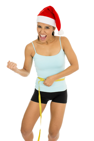 young attractive latin sport woman in fitness clothes and santa claus Christmas hat holding measure tape on body waist in diet and weight loss resolution concept isolated on white