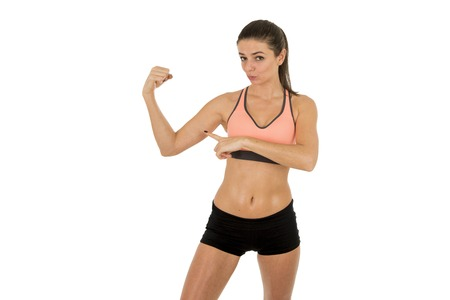 sport clothes: young attractive sport woman in fitness clothes smiling happy showing biceps posing isolated on white background in sport healthy lifestyle concept