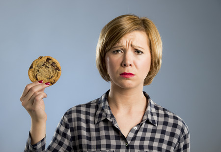 young blond cute and friendly caucasian woman in casual clothes holding big delicious chocolate cookie looking sad in temptation as thinking if ignoring diet and eating sweet junk food isolated background