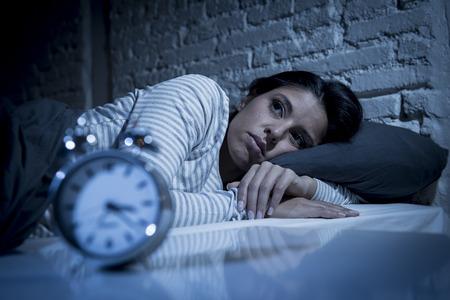 Mooie jonge Spaanse vrouw thuis slaapkamer in bed lag 's avonds laat proberen te slapen lijden slapeloosheid slaapstoornis of bang voor nachtmerries op zoek triest ongerust en benadrukte Stockfoto - 66884205
