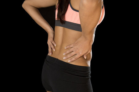grabbing at the back: young attractive hispanic fitness woman touching and grabbing her lower back suffering back pain isolated on black background in sport injury and body health care concept