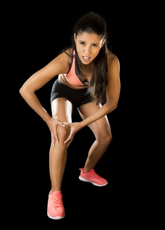contracture: young attractive sport woman holding injured knee suffering pain in ligaments injury or pulled muscle isolated on black background in fitness accident and body health care