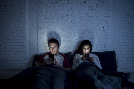 young couple at home in bed late at night using mobile phone in relationship communication problem and internet social media network concept