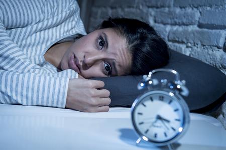 Joven mujer hispana hermosa en el dormitorio casa acostado en la cama por la noche tratando de dormir que sufren trastorno de insomnio o dormir de miedo en las pesadillas que parece triste preocupado y estresado Foto de archivo - 66884314