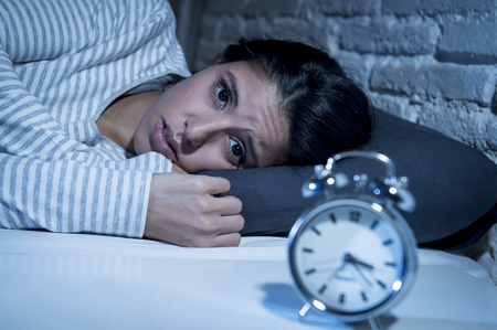 Mooie jonge Spaanse vrouw thuis slaapkamer in bed lag 's avonds laat proberen te slapen lijden slapeloosheid slaapstoornis of bang voor nachtmerries op zoek triest ongerust en benadrukte Stockfoto - 66884314