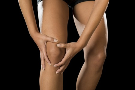 contracture: cropped close up view young sport woman holding injured knee suffering pain in ligaments injury or pulled muscle isolated on black background in fitness accident and body health care