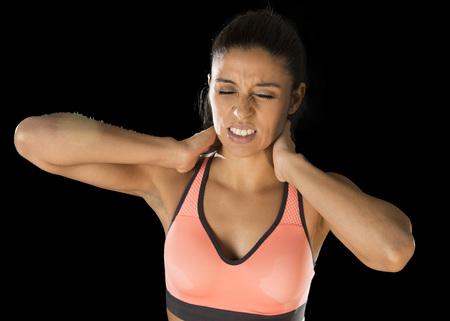 jonge aantrekkelijke Spaanse fitness vrouw aan te raken en grijpen haar nek en bovenrug lijden nekpijn geïsoleerd op een zwarte achtergrond in de sport letsel en lichaam zorgconcept