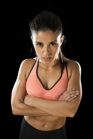 hispanic girl: young attractive sexy latin sport woman posing in fierce and badass face expression with fit slim body isolated on black background in healthy lifestyle and fitness concept