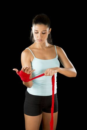 fierce competition: young attractive hispanic fitness woman doing self hand wraps before boxing or fighting workout isolated on black background looking fierce concentrated and confident