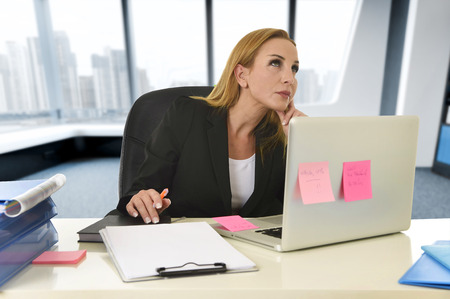 visualizing: attractive 40s blond businesswoman working at laptop computer sitting on the desk absent minded and thoughtful as if thinking of important business at modern office Stock Photo