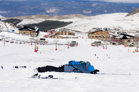 sierra nevada: young man lying on cold snow after ski crash at Sierra Nevada resort in Spain with mountains background in winter sport accident concept