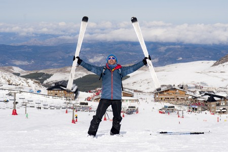 sierra nevada: young happy man in winter clothes and ski gear posing happy in snow mountains at Sierra Nevada resort in Spain in adventure sport and vacation destination concept Stock Photo