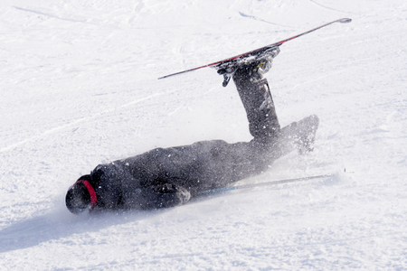 unskilled: young unskilled man falling on cold snow in ski crash at Sierrna Nevada resort in Spain in winter sport accident concept Stock Photo