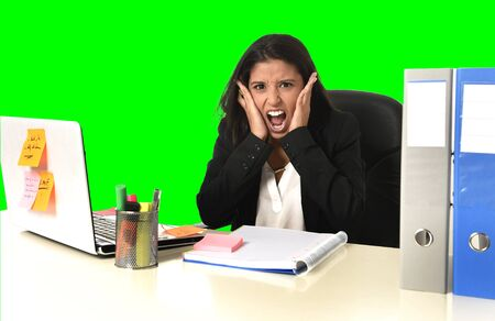 young beautiful latin business woman suffering stress working at office computer desk looking worried and desperate having problem at work isolated green chroma key background Stock Photo