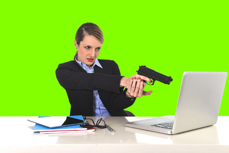 young attractive businesswoman pointing gun to computer laptop sitting at office desk desperate and stressed having problems with work project and technology isolated green chroma key Banco de Imagens