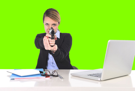 young attractive businesswoman sitting at office desk pointing gun in powerful boss attitude and killer employee concept isolated on green chroma key screen background