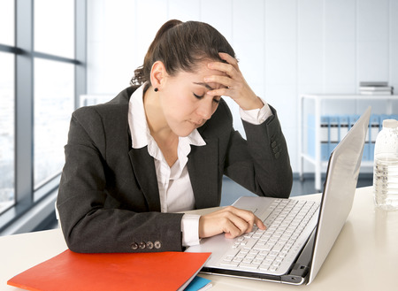 job deadline: overworked hispanic businesswoman wearing business suit working on  laptop computer at modern office room looking stressed and worried in woman facing work problem concept