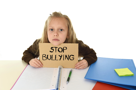 bullied: young beautiful schoolgirl scared in stress holding paper with text stop bullying  written looking desperate asking for help sitting at school desk alone in victim children bullied and abuse concept Stock Photo