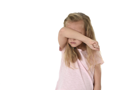 sweet young little schoolgirl covering her face with her arm crying sad victim of bullying at school isolated on white background