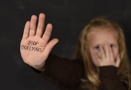 weaker: young little cute schoolgirl scared and sad asking for help showing hands with stop bullying text written on her palm in stress in front of school blackboard in education and childhood problem concept