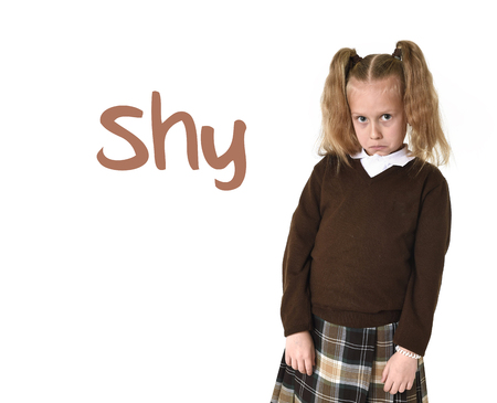 timid: English language learning vocabulary school card with word shy and young sweet little schoolgirl with pigtails in school uniform shy and timid as if scared or overwhelmed isolated on white