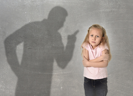 misbehavior: father or teacher shadow screaming angry reproving misbehavior to young sweet little schoolgirl or daughter with beautiful blonde hair sad intimidated looking scared and guilty isolated