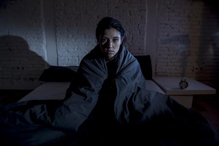 mooie jonge Spaanse vrouw thuis slaapkamer in bed lag 's avonds laat proberen te slapen lijden slapeloosheid slaapstoornis of bang voor nachtmerries op zoek triest ongerust en benadrukte