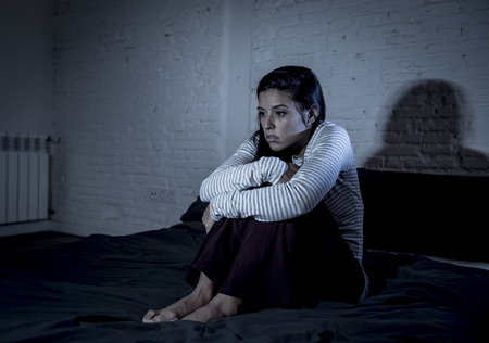 young beautiful hispanic woman at home bedroom lying in bed late at night trying to sleep suffering insomnia sleeping disorder or scared on nightmares looking sad worried and stressed