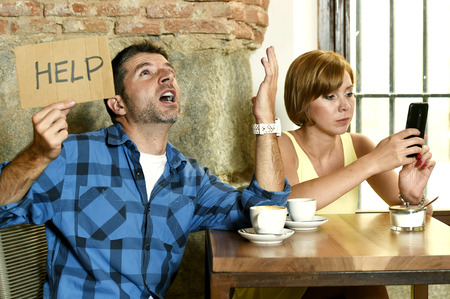 young American couple at coffee shop with internet and mobile phone addict woman ignoring bored sad and frustrated man boyfriend or husband in relationship problem asking for help Stock Photo