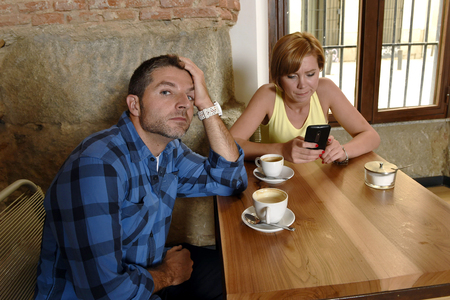 exasperated: young American couple at coffee shop with internet and mobile phone addict woman ignoring bored sad and frustrated man boyfriend or husband in relationship problem and addiction concept
