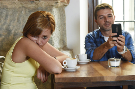 young American couple at coffee shop with internet and mobile phone addict man ignoring bored sad and frustrated woman girlfriend or wife in relationship problem and addiction concept Stock Photo