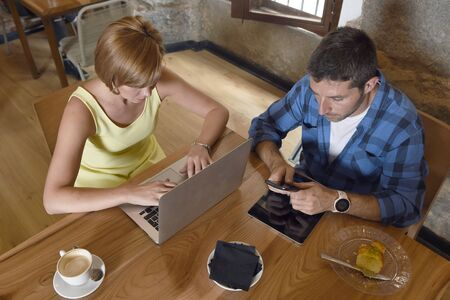 young American couple at coffee shop with man and woman close up hands using laptop computer and mobile phone networking ignoring each other in relationship communication problem