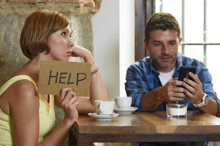 exasperated: young American couple at coffee shop with internet and mobile phone addict man ignoring bored sad and frustrated woman girlfriend or wife in relationship problem and addiction concept Stock Photo