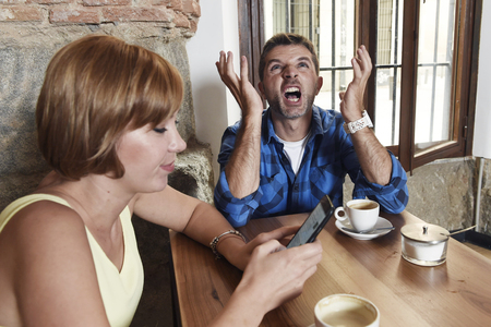 exasperated: young American couple at coffee shop with internet and mobile phone addict woman ignoring bored desperate and frustrated man boyfriend or husband in relationship problem and addiction concept