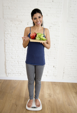food tray: young attractive slim latin woman or teenager girl checking weight on scale holding vegetable tray smiling happy and satisfied in weight loss success and diet concept