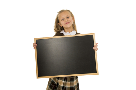 nine years old: 7 or 8 years old little beautiful blond schoolgirl smiling happy and cheerful holding and showing small blank blackboard with copy space in child school education concept isolated on white background