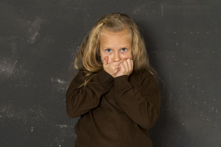 eight years old: 7 or 8 years old little beautiful blond schoolgirl sad moody and tired in front of school class blackboard in child school education concept isolated on white background Stock Photo