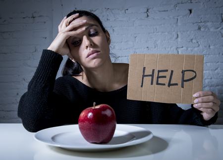 refusing: young woman or teen looking apple fruit on dish as symbol of crazy diet in nutrition disorder concept anorexia and bulimia and refusing to eat food in diet calories obsession asking for help