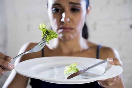 jonge vrouw of tienermeisje dat schotel met belachelijk weinig sla als haar voedsel symbool van gekke dieet in de voeding wanorde concept van anorexia en boulimia en het weigeren om te eten in de voeding calorieën obsessie
