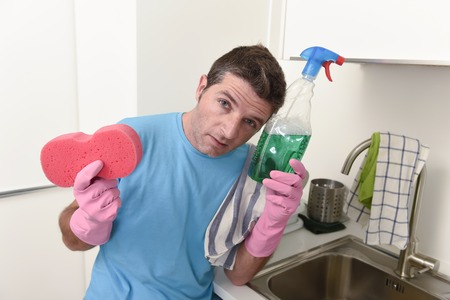 young lazy house cleaner man washing and cleaning the kitchen with detergent spray bottle and sponge in stress and desperate face expression in male housework and housekeeping concept Stock Photo