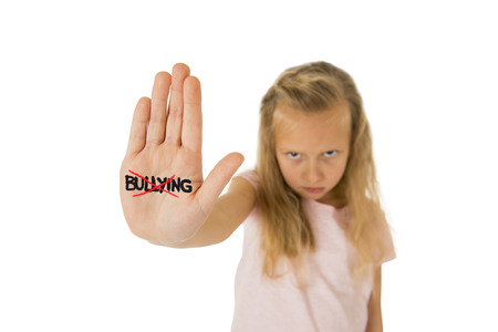 nine years old: sweet and scared little schoolgirl showing the word bullying scratched written in her hand in the concept children bullied and abused in school isolated on white background
