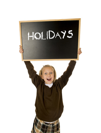 7 8: 7  8 years old little beautiful blond schoolgirl smiling happy and cheerful holding and showing small blackboard with text holidays in end of school and education concept isolated white Stock Photo