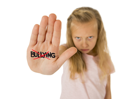 bullied: sweet and scared little schoolgirl showing the word bullying scratched written in her hand in the concept children bullied and abused in school isolated on white background