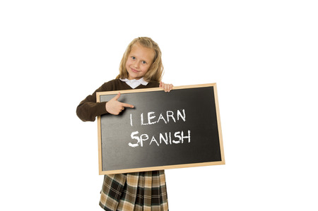 7 8: 7  8 years old little beautiful blond schoolgirl smiling happy and cheerful holding and showing small blackboard with text I learn Spanish in language education concept isolated white
